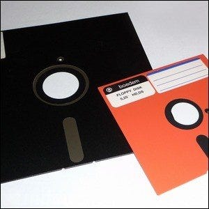 An 8 inch and 5.25 inch floppy disk laying on a table together.
