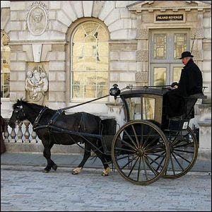 A Hansom cab and driver that were a part of period filming for a Sherlock Holmes movie at Somerset House in London.