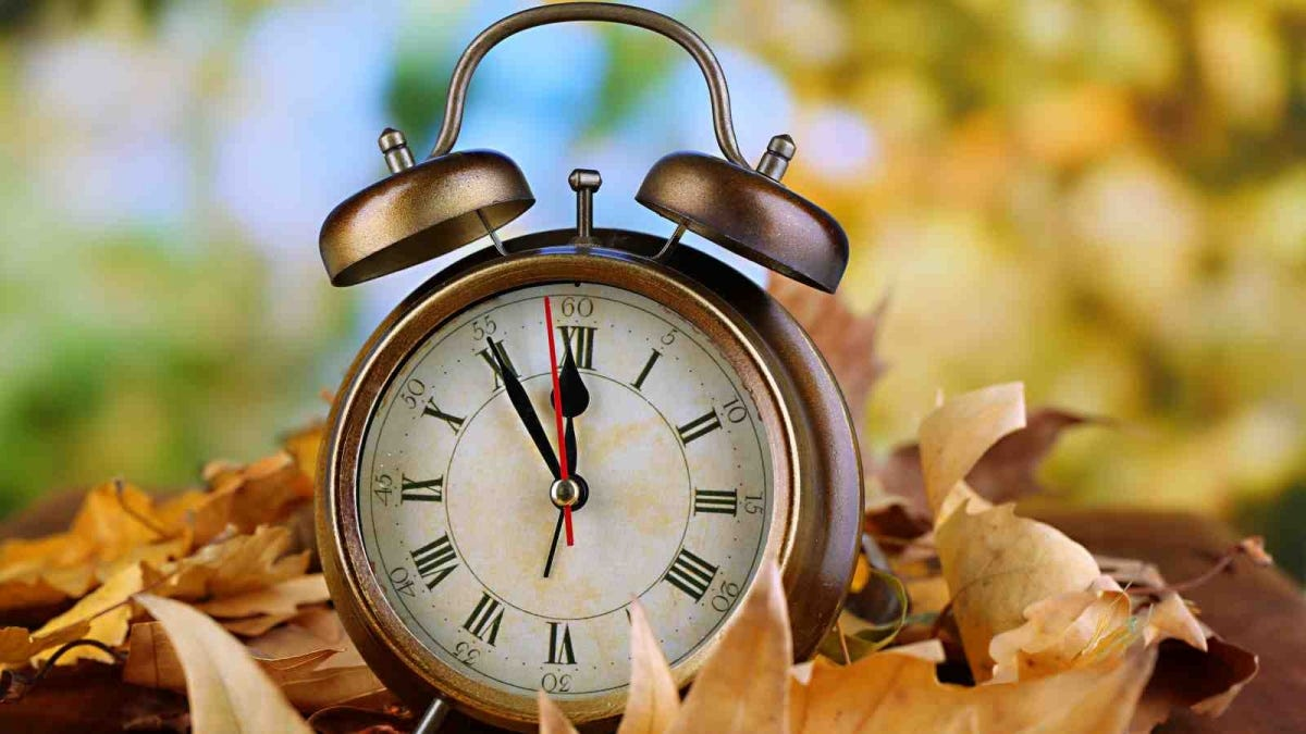 Old clock on autumn leaves on wooden table on natural background