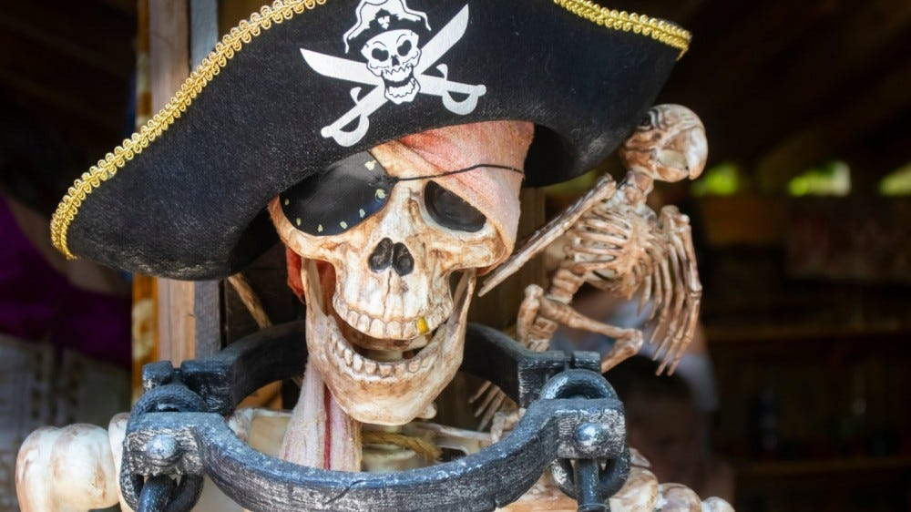 Pirate skeleton fastened to post with manacle with skeleton bird on shoulder