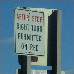"""An example of a right turn sign reading, """"After stop, right turn permitted on red."""""""