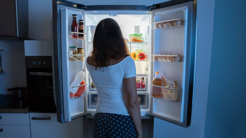 Rear View Of Young Woman Looking In Fridge