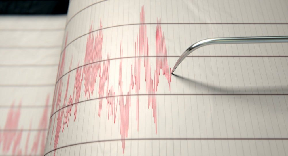 loseup of a seismograph machine needle drawing a red line on graph paper