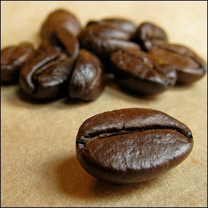A close-up view of recently roasted coffee beans laying on brown paper.